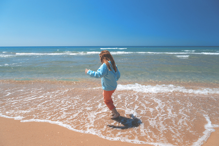 Little girl on the sea beach. Concept - Goodbye summer. Off-season.