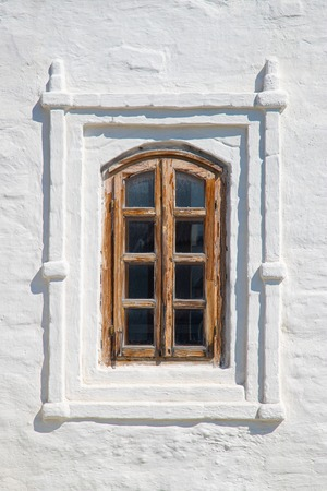 An old wooden window on a stone wall