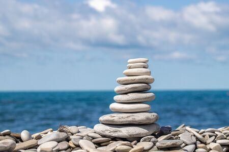 Une pile de cailloux colorés sur le fond le ciel et la mer
