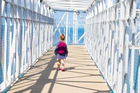 Little girl runs across the bridge Reklamní fotografie