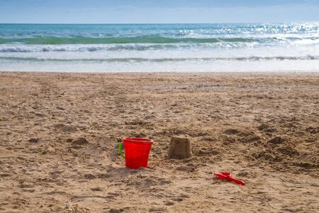 A plastic red bucket lies on the sand of an empty beach Losing a child or saying goodbye to summer