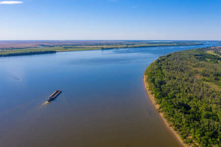 A barge or dry cargo ship goes upstream of the Volga River near Astrakhan. Aerial photography. High quality photo Stock fotó