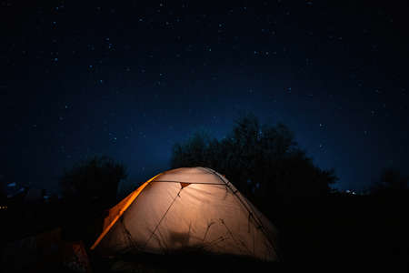 Tent with light on the countryside at night with stars. Illuminated yellow tent on the grass under a beautiful sky. Travel and adventure concepts. High quality photo