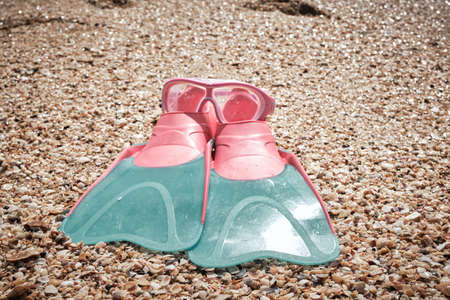 A snorkeling mask and baby flippers on the beach sand. High quality photo