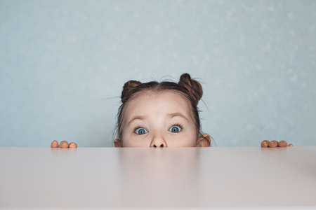 Portrait of little girl looking from under the table. High quality photo