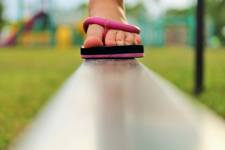 child s: Child s foot, wearing a flip flop, walking on a balance beam