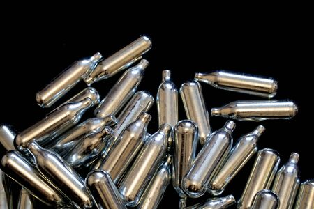 Nitrous Oxide Metal Bulb Canisters Recreational Drugs on Black Background Stok Fotoğraf