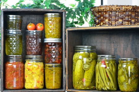 Two wooden boxes full of a Variety of country home preserved items made from fresh garden vegetables. photo