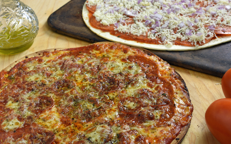 バック グラウンドでを焼く準備ができたと調理済みピザ