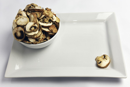 Sliced mushrooms in a bowl on white background Stockfoto