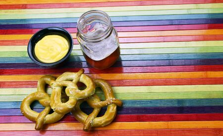 Craft Beer With Pretzel and Cheese on a rainbow background