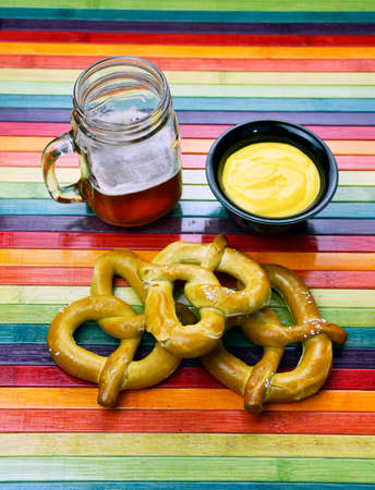 Hand-crafted red ale with homemade pretzel and cheese fondue on a rainbow background