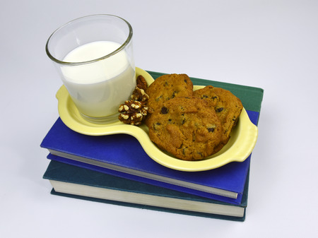 Books with cookies and milk on white background