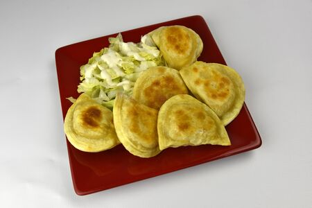Cheese and potato filled pierogies dumplings on white background
