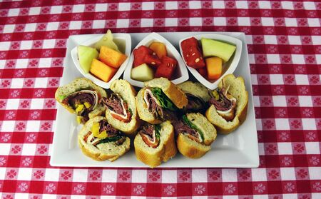 Italian roast beef sandwich appetizer with fresh fruit on red checkered tablecloth