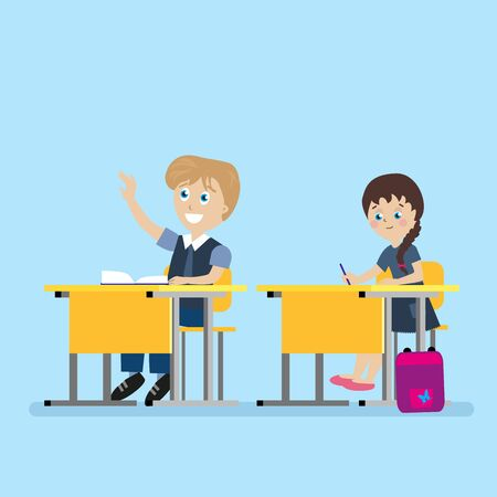 school: Schoolchild sits at a school desk during lessons with his hand raised.