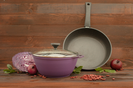 Aluminum non-stick cookware with vegetables on wooden background