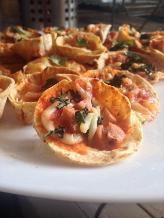 mini pizza: Homemade mini pizza with tomato base, sausage, mozzarella and basil leaf toppings. Stock Photo