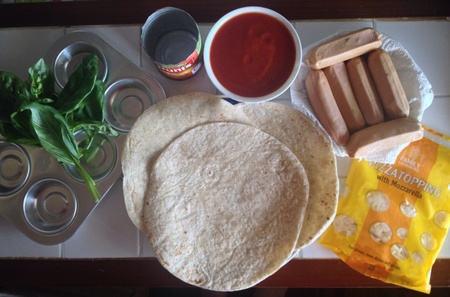 tomato paste: Ingredients for a simple and tasty meal. Homemade mini pizzas with tortilla base, tomato paste, basil leaves, and sausages.
