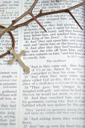 crucify: Good Friday, crucifixion scripture background. Closeup of King James version Bible page. Open to the gospel of Matthew, chapter 27. Silver colored cross laid across page.With thorns to remind of the crown of thorns Christ wore. Stock Photo