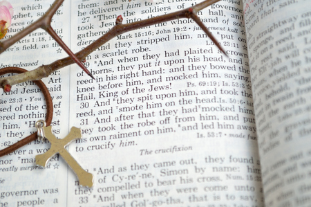 king james: Good Friday, crucifixion scripture background. Closeup of King James version Bible page. Open to the gospel of Matthew, chapter 27. Silver colored cross laid across page.With thorns to remind of the crown of thorns Christ wore. Stock Photo