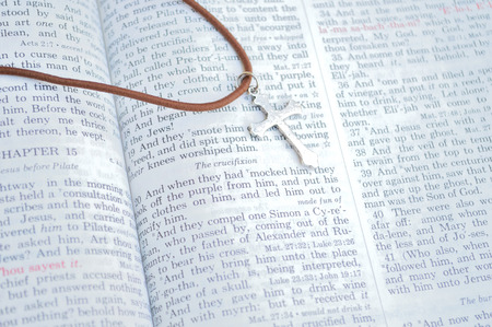 king james: Good Friday, crucifixion scripture background. Closeup of King James version Bible page. Bible open to the Gospel of Mark, chapter 15. Silver colored cross on brown chain.