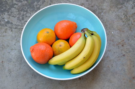 valencia orange: Bananas, valencia oranges, and tangelos in a large turquoise blue bowl with white rim, sitting on a concrete surface in the sunlight. Fresh, ripe, tropical fruit