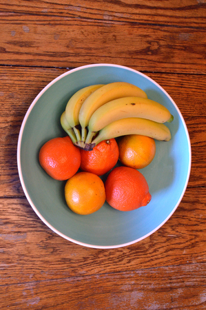 valencia orange: Bananas, valencia oranges, and tangelos in a large turquoise blue bowl with white rim, sitting on a wood table Stock Photo