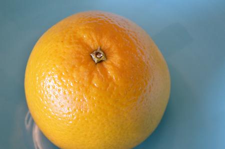 valencia orange: A single valencia orange in a blue bowl, closeup