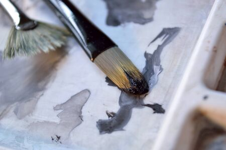 filbert: Two paintbrushes on a white artists paint palette, fan brush and filbert brush.
