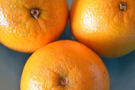 valencia orange: 3 Valencia oranges, extreme closeup