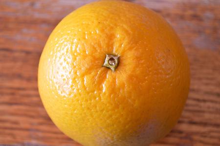 valencia orange: Closeup of Valencia orange on a wood table