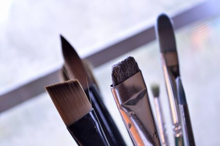 fine tip: Bouquet of six paintbrushes of various sizes and shapes, standing upright in art studio.