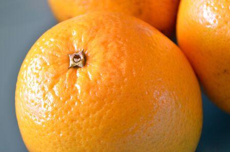 valencia orange: Valencia oranges in a blue bowl, extreme closeup Stock Photo