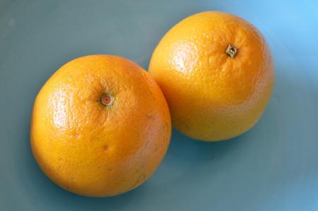 valencia orange: Two valencia oranges in a blue bowl