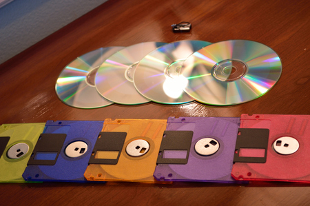 progression: Floppy disks, cd roms, and a flash drive, showing progression of technology. Stock Photo