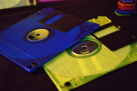disks: Neon blue and yellow floppy disks with black background