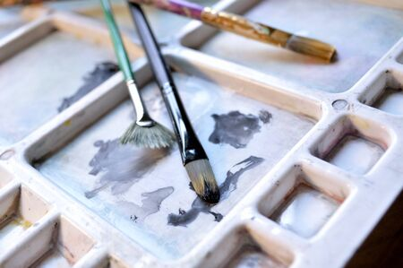 Three paintbrushes on an artists paint palette with gouache and watercolor paint