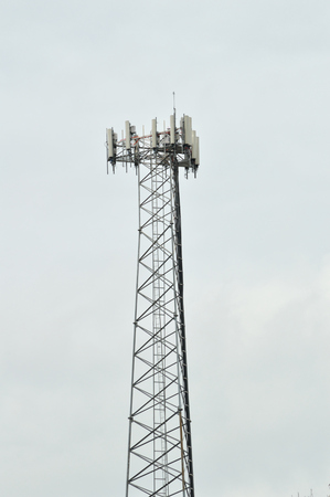 wireless tool: Cell phone tower against an overcast sky. Useful telecommunications photo, in a vertical orientation. Modern, industrial.