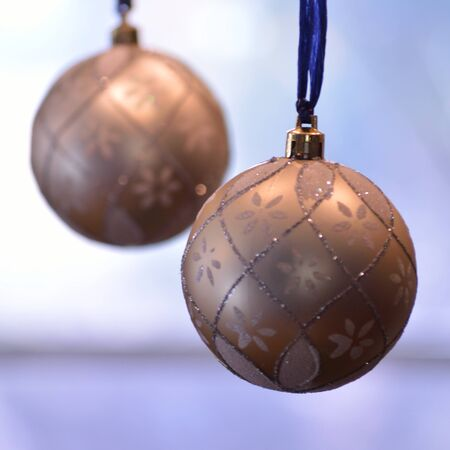 Two gold and silver christmas balls hanging from blue cords against a lit background.