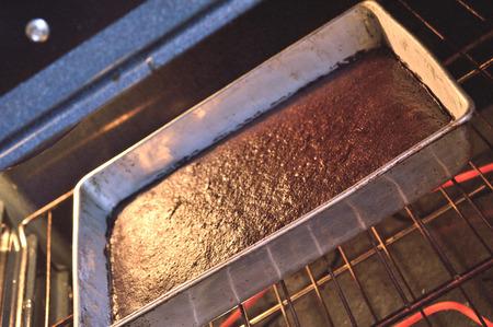 metal sheet: Dark chocolate sheet cake baking in metal pan in the oven.