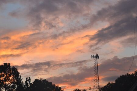 pinks: Beautiful sunset photo with clouds in grays, blues, pinks, and oranges, with cell phone tower silhouette in foreground.