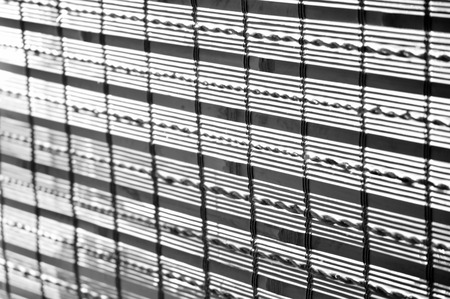 window shade: Black and white closeup of a window covered with a bamboo window shade. Stock Photo