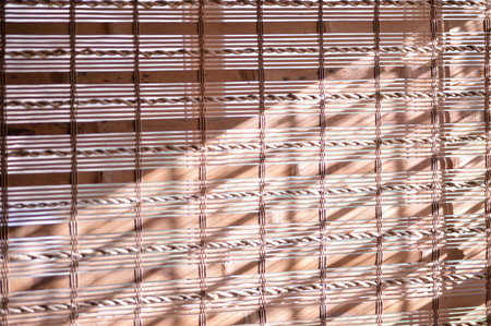 window shades: Bamboo shades covering window with sunlight shining on them