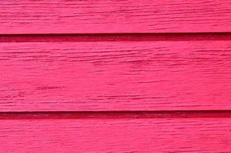 Wood slats running horizontal, distressed, chipping paint job, in hot pink.
