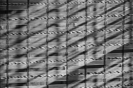 filtering: Textured background of woven bamboo window shades with sun rays filtering across them. Black and white.