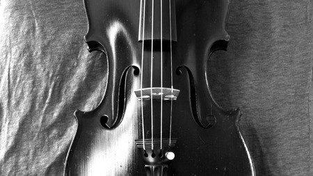 bluegrass: Black and white closeup of violin against a linen background. Violin is an antique from the early 1800s in a dark stain (original finish).
