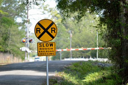 railroad crossing: Railroad crossing sign on a rural road with railroad crossing in the background. Railroad crossing arms are down and crossing lights are on as train is approaching the crossing. Concept photo of life circumstances and troubles we face.