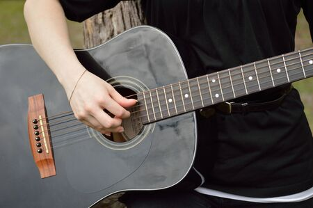 Person playing a black acoustic guitar 写真素材