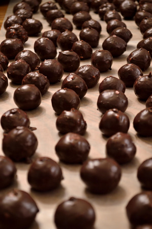 martha: Hand-dipped, chocolate Martha Washington candy (also know as chocolate bon-bons) layed out on wax paper in rows to dry.